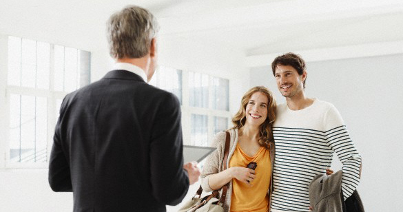 Real estate agent showing happy young couple their new sun filled modern home